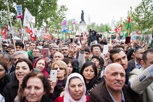 A crowd listens to Selahattin Demirtas, leader of the Turkish pro-Kurdish Peoples' Democratic Party (HDP), speak at a campaign rally, Paris, France, May 2, 2015 (Photo by Aurore Belot/NurPhoto via AP).